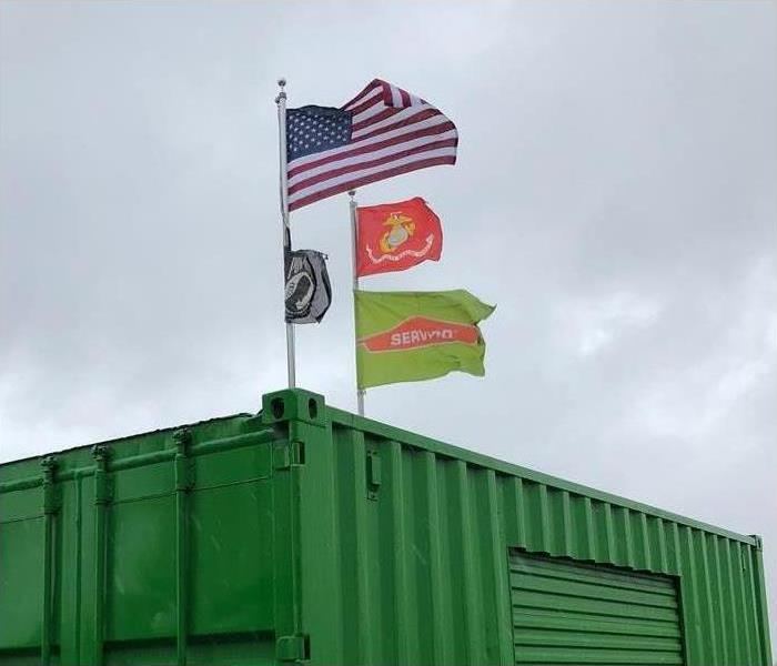 SERVPRO, USMC and POW MIA flag flying in the gloomy sky.
