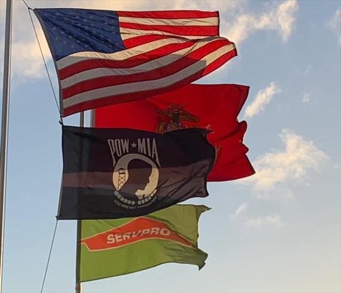 Four flags blowing in wind: USA, POWMIA, USMC, SERVPRO