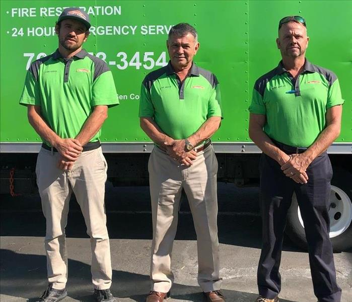 Three men dressed in green in front of a green truck.