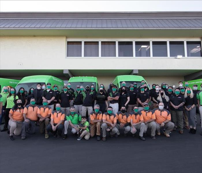 Group photo of employees with mask on in front of green trucks.