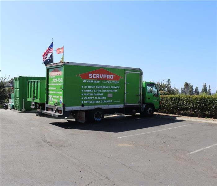 Green SERVPRO truck in parking lot with flags flying in background.